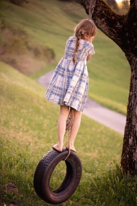 girl playing on tire swing copy